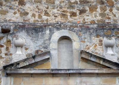 Frontón triangular partido sobre el acceso principal