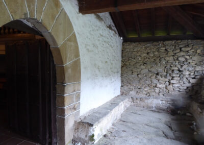 Pórtico  con estructura de madera y lajas de piedra reaprovechadas en el suelo