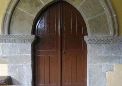 Acceso lateral gótico en arco apuntado bajo el pórtico