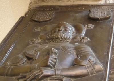 Figura yacente de caballero barbado con la espada en las manos