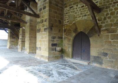 Acceso lateral apuntado y dovelado del siglo XV